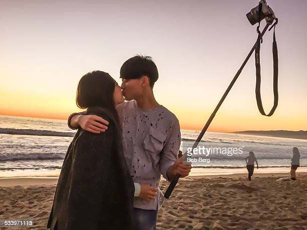 Santa Monica Ca January 16 2015 A Japanese couple on vacation take a couple selfie with a selfie stick and kiss
