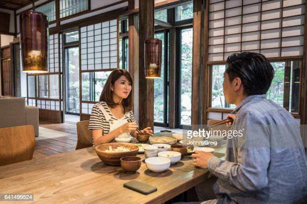 Japanese couple sitting at dinner table enjoyming meal