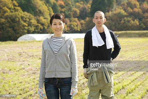 Japanese couple standing in field, portrait