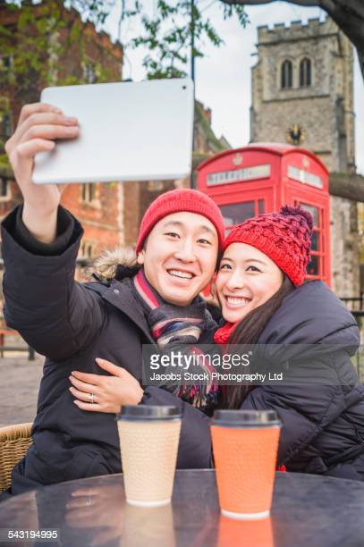 Japanese couple taking selfie with digital tablet