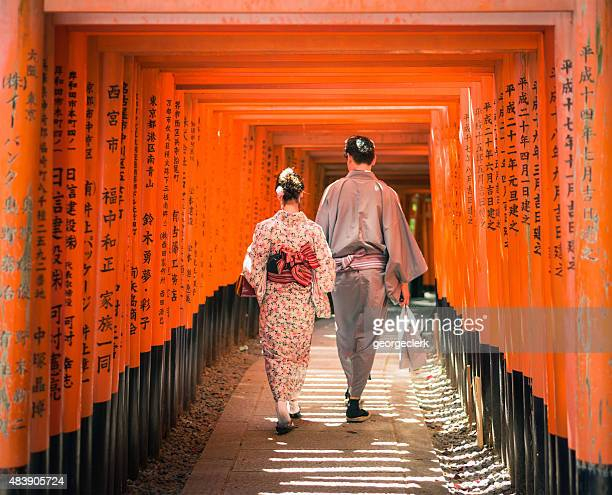 Japanese couple walking through Torii gates at Fushimi Inari-Taisha