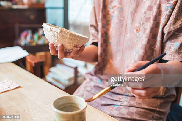 Japanese Craftsperson painting a paper bowl