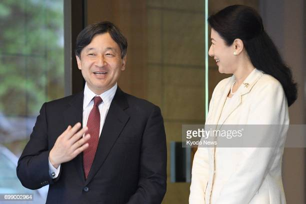 Japanese Crown Prince Naruhito and his wife Crown Princess Masako are seen at the entrance of their residence in Tokyo on June 21 after the crown...