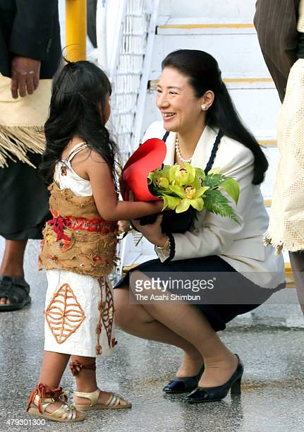 Japanese Crown Princess Masako receives a flower bouquet from a girl upon arrival at Fua'amotu International Airport on July 3 2015 in Nuku'alofa...