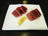 Still image of Japanese cuisine -  slices of  fresh tuna sashimi / maguro served on white plate with dark background