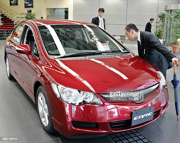 Japanese customer checks Japanese auto giant Honda's newly released compact sedan 'Civic' at the company's showroom in Tokyo 27 October 2005 AFP...