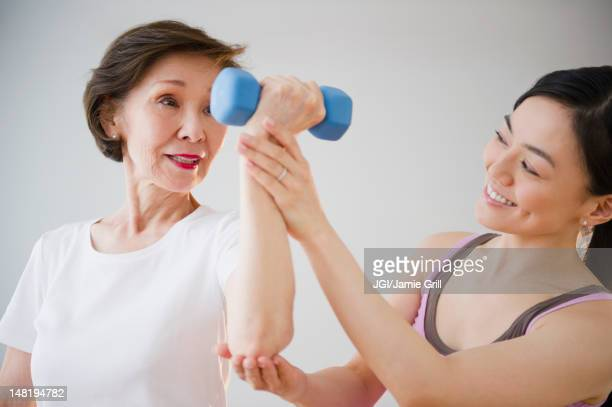 Japanese daughter helping mother with exercise