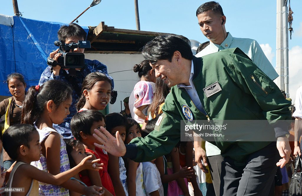 Japanese Defense Minister Itsunori Onodera visits children displaced by Typhoon Haiyan at an evacuation center on December 8, 2013 in Talcoban, Leyte, Philippines.