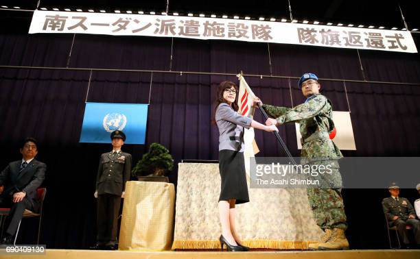 Japanese Defense Minister Tomomi Inada receives the flag during the JGSDF South Sudan Peaacekeeping Mission Completion Ceremony at the Defense...