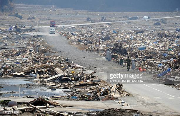 A Japanese defense soldier walks on the recently opened road running through the March 11 tsunami debris and destruction at the Otomo area in...