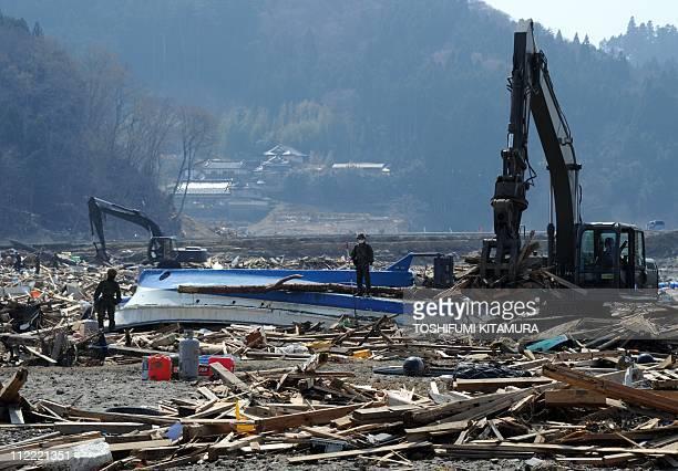 Japanese defense soldiers remove March 11 tsunami debris covering rice fields at the Otomo area in Rikuzentakata city Iwate prefecture on April 15...