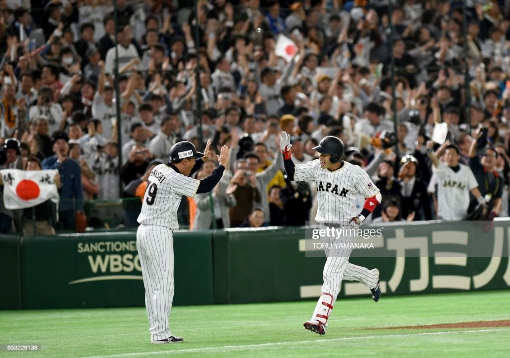 Japanese designated hitter Tetsuto Yamada (R) is congratulated by coach Takayuki Ohnishi (L) after hitting a two-run homer in bottom of the eighth inning during the World Baseball Classic Pool E second round match between Cuba and Japan at Tokyo Dome in Tokyo on March 14, 2017. /