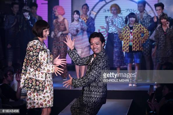 TOPSHOT Japanese designer Yukihiro Teshima gestures as members of Japanese girl pop music group Yumemiru Adolescence and models look on after...