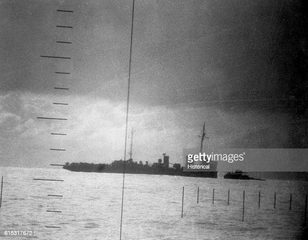 A Japanese destroyer sinks water rising over the top deck after being hit in the forward quarter by a torpedo from a US submarine   View from...
