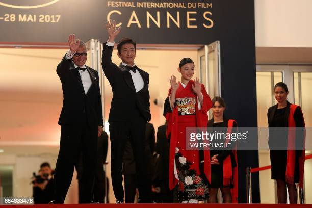 Japanese director Takashi Miike Japanese actor Takuya Kimura and Japanese actress Hanna Sugisaki wave on May 18 2017 as they arrive for the screening...