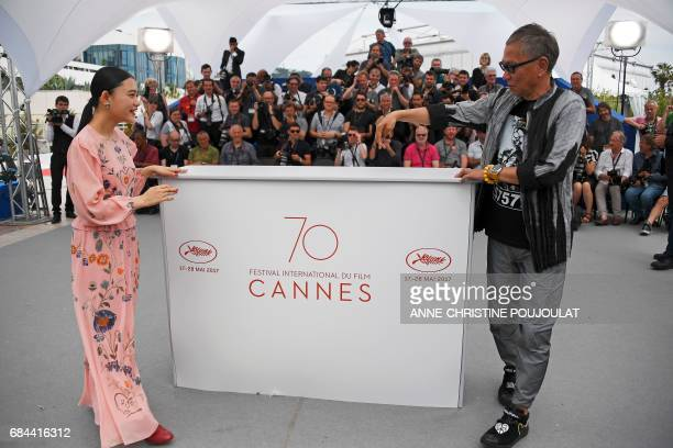Japanese director Takashi Miike talks on May 18 2017 with Japanese actress Hana Sugisaki as they pose during a photocall for the film 'Blade of the...