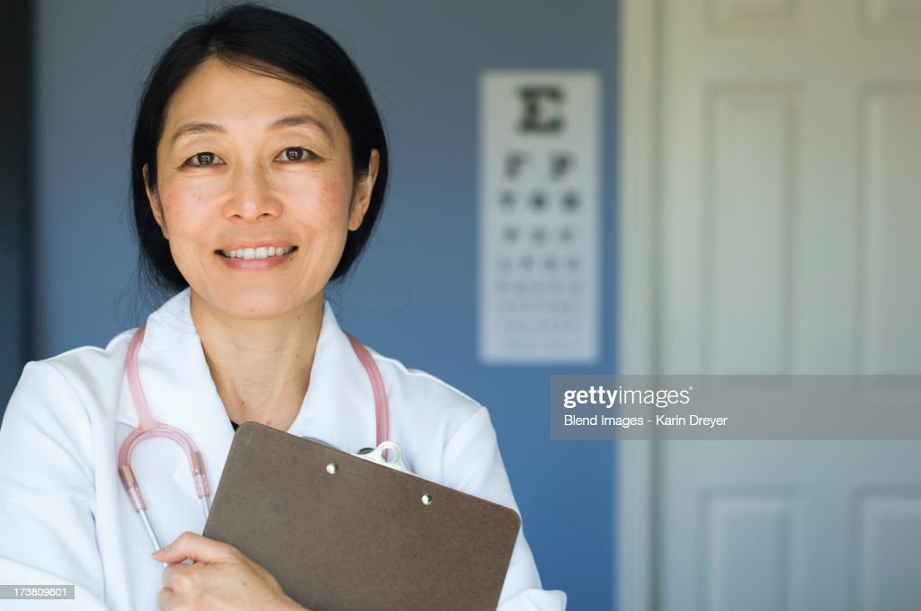 Japanese doctor standing in office : Stock Photo