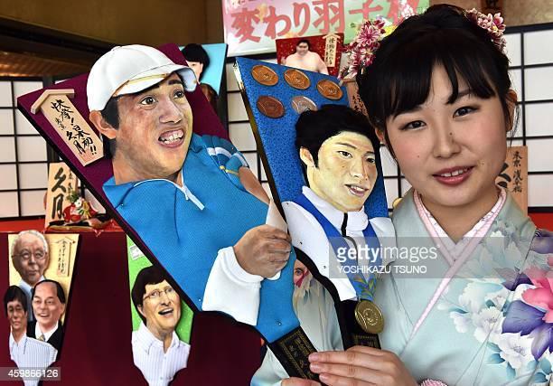 Japanese doll maker Kyugetsu employee Saeko Koyama wearing a kimono dress displays an ornamental wooden racket or 'hagoita' decorated with a...