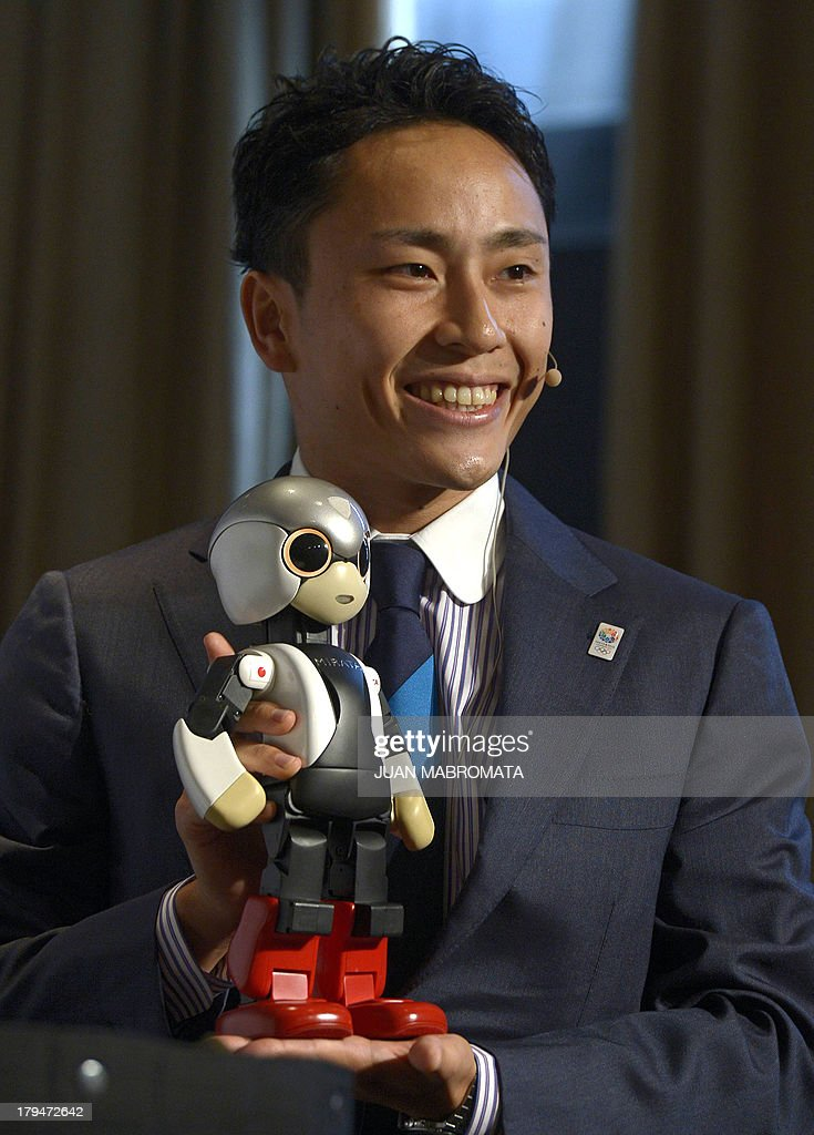 Japanese double silver fencing medallist Yuki Ota holds the robot Mirata as he poseS for photographers during a news conference given by IOC member and President of Japanese Olympic Committee and Tokyo 2020 candidate city Tsunekazu Takeda and President of Japan Sports Association Fujio Cho in Buenos Aires, Argentina on September 4, 2013, where the International Olympic Committee will elect the host city of the 2020 Summer Olympic Games on September 7 also will consider adding a new sport for the 2020 Olympic program and elect a new president on September 10.
