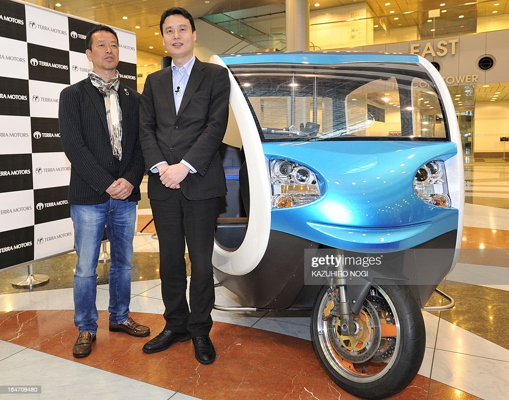 Japanese electric vehicle manufacturer Terra Motors President Toru Tokushige (2nd L) andformer Apple Japan CEO Kenji Yamamoto (L) poses with the company's prototype model of an EV Tricycle Taxi during a press preview in Tokyo on March 27, 2013. The taxi carries 6 passengers and the Japanese venture is confident in winning a big slice of the tuk-tuk market in Asia. AFP PHOTO / KAZUHIRO NOGI