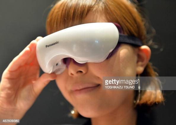 Japanese electronics giant Panasonic employee displays the new eye steamer 'EHSW53' that provides hot steam in Tokyo on July 22 2014 Panasonic will...