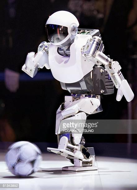Japanese electronics giant Sony's small humanoid robot SDR3X kicks a soccer ball at the robot exhibition 'Robodex' in Yokohama 23 November 2000 The...