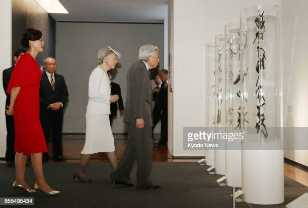 Japanese Emperor Akihito and Empress Michiko accompanied by calligraphy artist Sisyu look at her work at the Museum of Art Ehime in western Japan on...