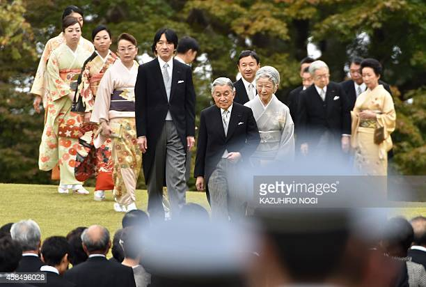 Japanese Emperor Akihito and Empress Michiko and the imperial family members walk towards guests during the annual autumn garden party at the Akasaka...