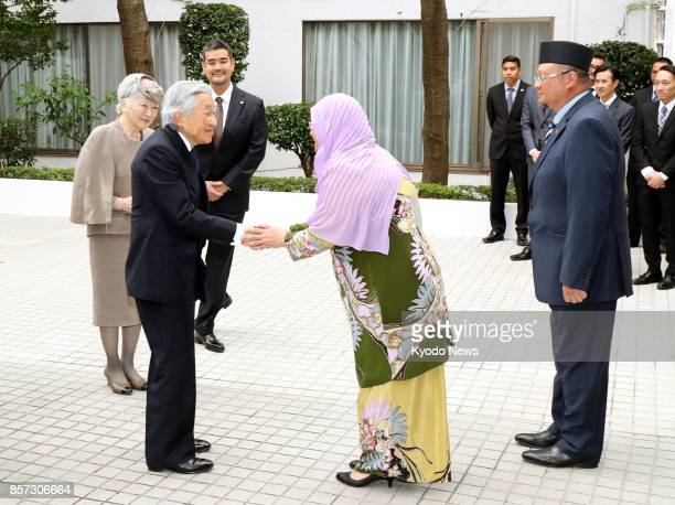 Japanese Emperor Akihito and Empress Michiko are greeted by Kamilah Hanifah Brunei's ambassador to Japan and her husband at the Bruneian Embassy in...