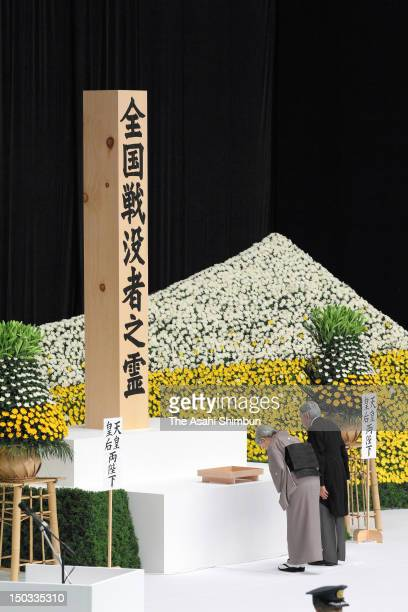 Japanese Emperor Akihito and Empress Michiko bow before the main altar decorated with huge bank of chrysanthemums as they offer prayers for the war...