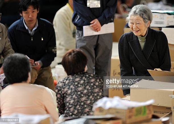 Japanese Empress Michiko smiles as she talks with evacuees from Futaba in Fukushima prefecture at their makeshift shelter in Kazo Saitama prefecture...