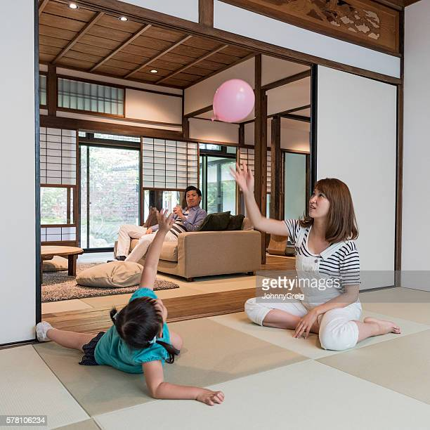 Japanese family at home, mother and daughter playing with balloon