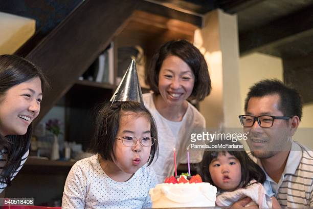 Japanese Family Celebrating Birthday with Cake and Candles at Home