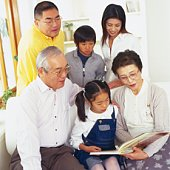 Japanese family in living room looking at photo album together, High Angle View, Front View