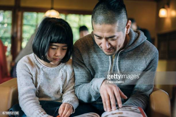 Japanese family reading a book together