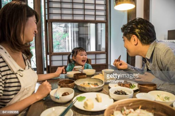 Japanese family sitting at dining table eating dinner