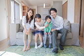 Japanese family sitting on sofa
