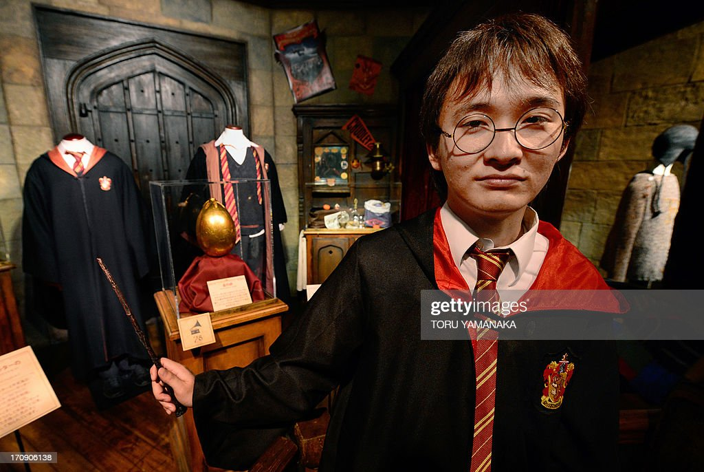 Japanese fan Yuki Nagata poses in front of Harry Potter costumes during the preview of a Harry Potter exhibition in Tokyo on June 20, 2013. The exhibition will be held from June 22 to September 16. AFP PHOTO / Toru YAMANAKA