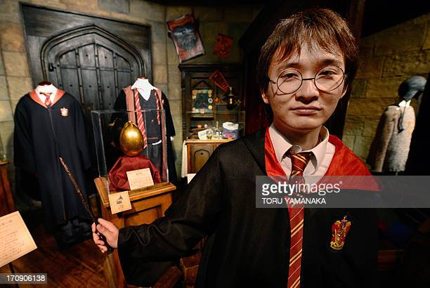 Japanese fan Yuki Nagata poses in front of Harry Potter costumes during the preview of a Harry Potter exhibition in Tokyo on June 20 2013 The...