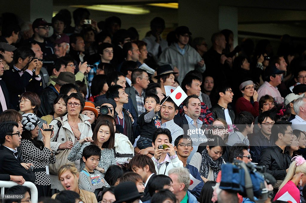 Japanese fans are seen holding flags in the crowd as they attend The Qatar Prix de l'Arc de Triomphe at Hippodrome de Longchamp on October 6 2013 in...