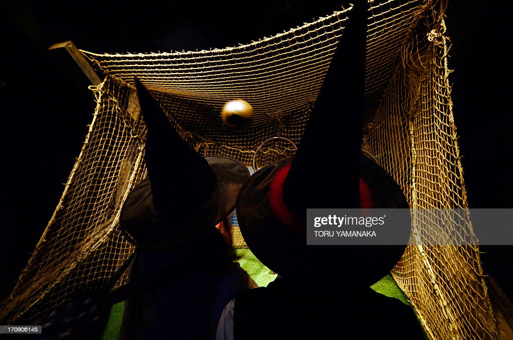 Japanese fans clad in witch hats throw a ball to experience 'quidditch', the most popular sport in the wizarding world, during the preview of the Harry Potter exhibition in Tokyo on June 20, 2013. The exhibition will be held from June 22 to September 16. AFP PHOTO/Toru YAMANAKA