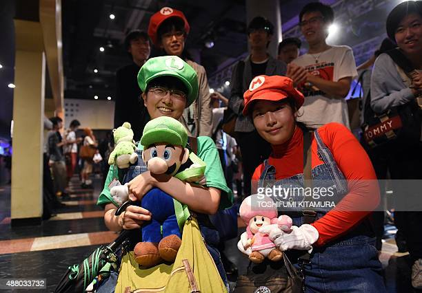 Japanese fans holding dolls and wearing costumes attend a live performance of the most wellknown Super Mario music to mark the game's 30th...