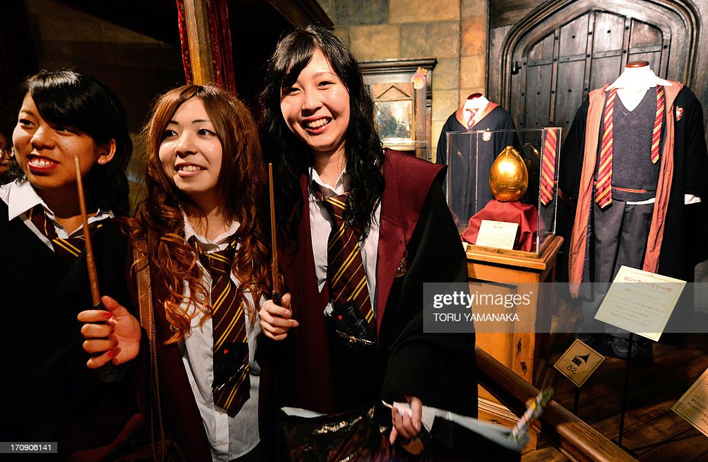 Japanese fans pose in front of Harry Potter costumes during the preview of the Harry Potter exhibition in Tokyo on June 20, 2013. The exhibition will be held from June 22 to September 16. AFP PHOTO/Toru YAMANAKA