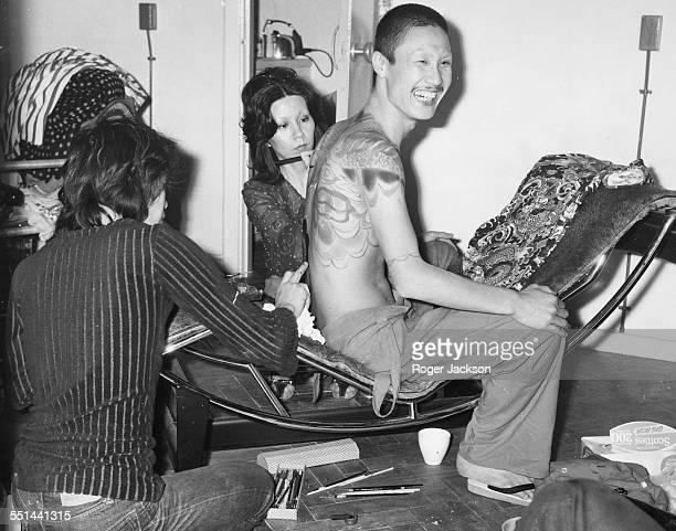 Japanese fashion designer Kansai Yamamoto having his back painted by assistants at his Boston 151 boutique on Fulham Road London May 12th 1971
