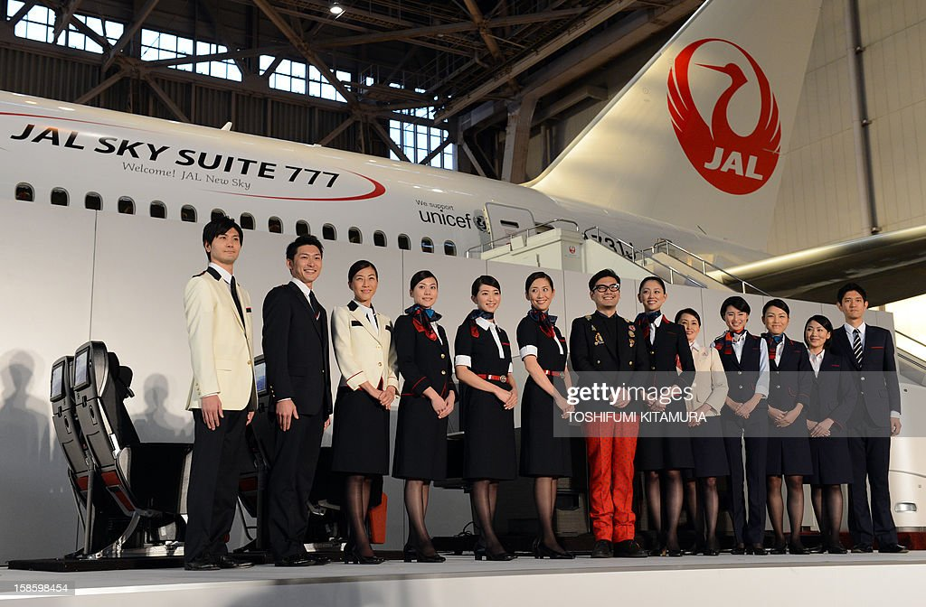 Japanese fashion designer Keita Maruyama (C) and Japan Airlines cabin attendants (L) and ground service staff (R) pose in their new uniforms during a photo session during the company's press preview in their maintenance centre at the Tokyo International Airport in Tokyo on December 20, 2012. JAL displayed their new uniforms and new 'JAL SKY SUIT 777' seats for all cabin categories of their new Boeing 777-300ER jetliners during the press preview.