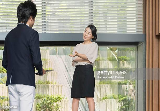 Japanese Female Boss Speaking to Male Employee in Office Lobby