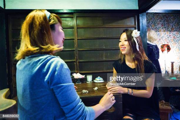 Japanese female customer tries on hair decoration at Japanese curio store