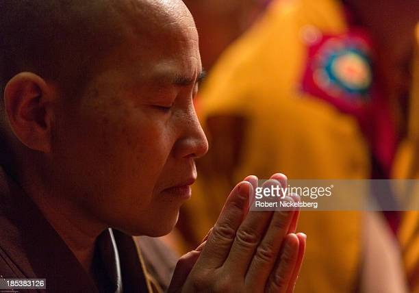 Japanese female monk prays while attending the Dalai Lama teachings at the Beacon Theater October 19 2013 in New York City The Dalai Lama is in New...