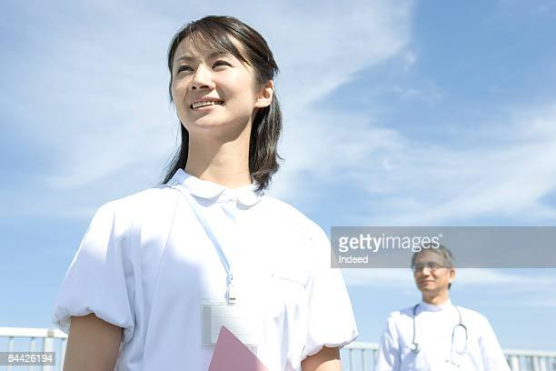 Japanese female nurse smiling and looking away