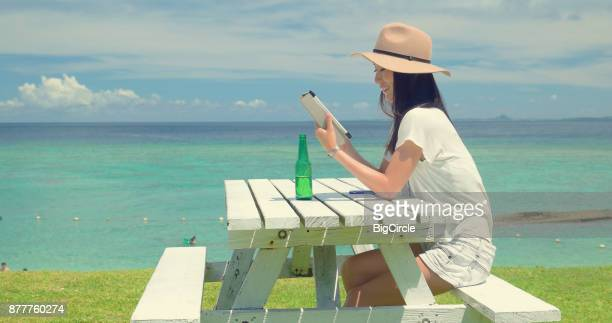 Japanese female sitting by the beach.